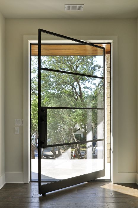 thin black iron framed pivot front door